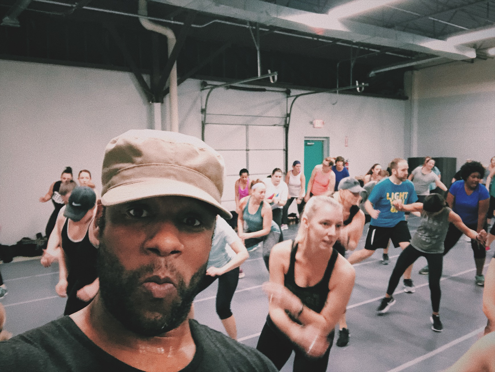 M. Nicholson hip hop fitness instructor Mike Nicholson looks at the camera while people are performing moments in his dance fitness class