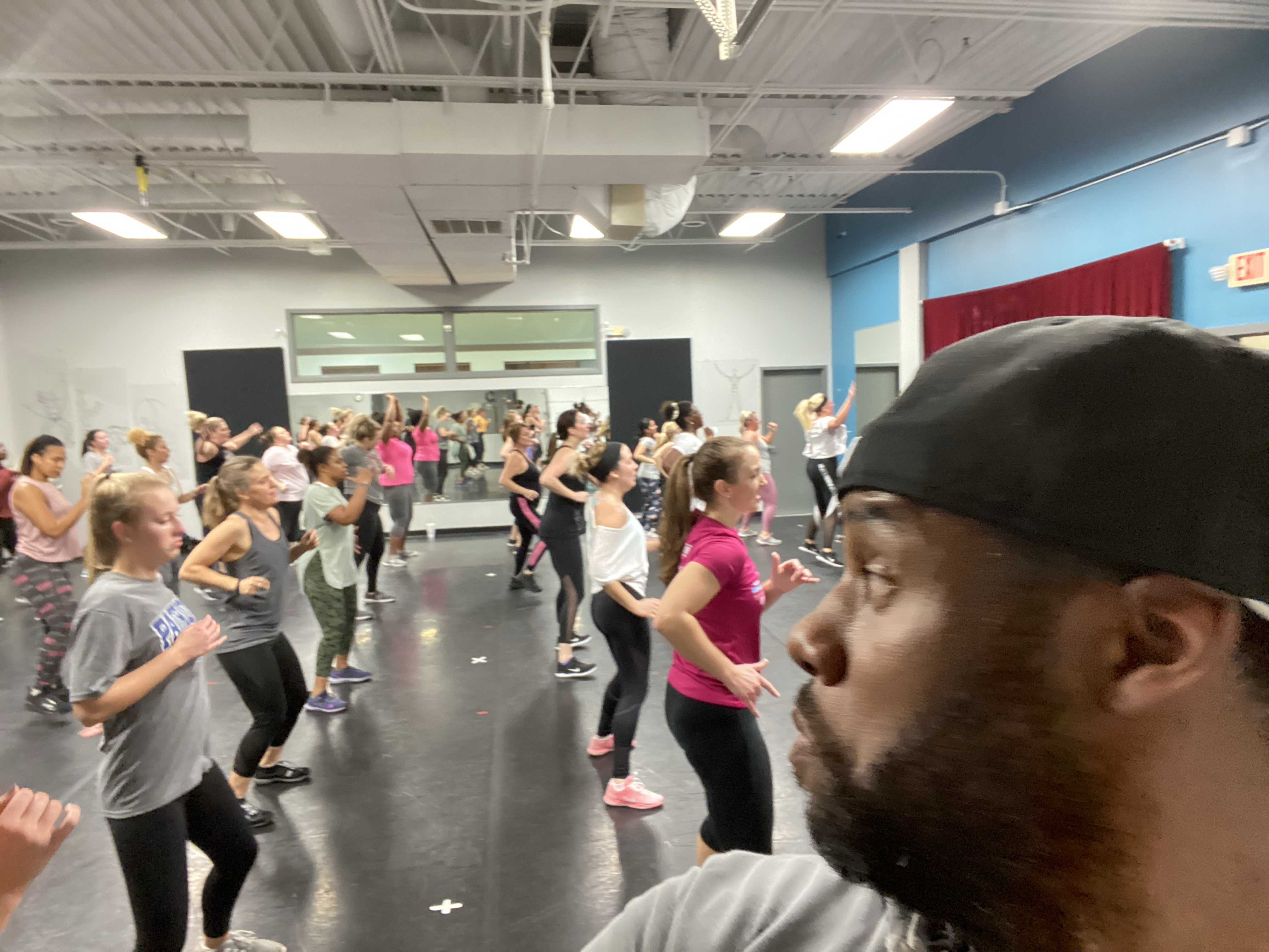 M. Nicholson hip hop fitness instructor Mike Nicholson wearing a black baseball cap turned backward overlooking the class full of people doing dance fitness in Columbus Ohio